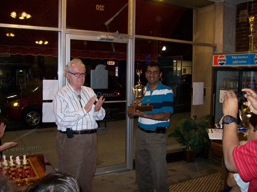 Surya Kopula is presented with a Champion trophy.